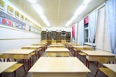 Tabelas e cadeiras dentro da classe de escola Fotos de Stock