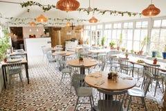Tabelas e cadeiras em um restaurante vazio na luz do dia brilhante fotografia de stock royalty free