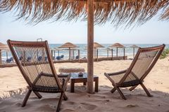 Tabelas e cadeiras estabelecidas na praia Cargo de madeira com o guarda-chuva tropical que está acima Brisa do oceano que balança fotos de stock royalty free