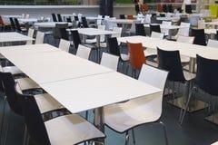 Tabelas e cadeiras vazias no areea do fast food Fotografia de Stock