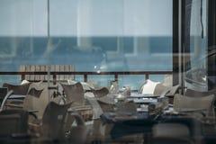 Tabelas em um restaurante com opiniões da praia e do mar Imagens de Stock