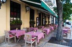Tabelas exteriores em um café ou em um restaurante local Fotografia de Stock
