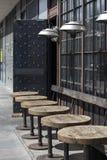 Tabelas fora no café urbano com as lâmpadas modernas no estilo de Art Nouveau Fotografia de Stock