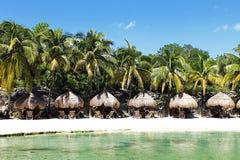 Tabelas na praia com guarda-chuvas cobridos com sapê Fotos de Stock Royalty Free