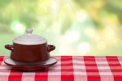 Tabellöverkant på bunkebakgrund Tom brun keramisk soppabunke på plattan med locket på en röd rutig bordduk över abstrakt ljust arkivfoto
