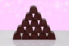 Tabellöverkant på chokladsötsaker Closeup av pyramiden som göras från chokladkonfekt på en vit tabell över abstrakta ljusa rosa f royaltyfria bilder