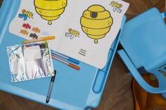 Tabell för barn` s med tuschpennor och ark av papper royaltyfri foto