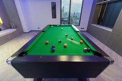 Tabell för biljard för rörelsesnookerpöl grön med den färdiga uppsättningen av bollar i en mitt av en lek i ett modernt lekrum fotografering för bildbyråer