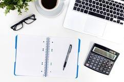 Tabell för kontorsskrivbord med bärbara datorn, kaffekoppen och bästa sikt för tillförsel royaltyfri foto