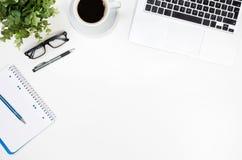 Tabell för kontorsskrivbord med bärbara datorn, kaffekoppen och bästa sikt för tillförsel Fotografering för Bildbyråer