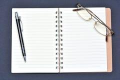 Tabell för kontorsskrivbord med den öppet anteckningsbokpapper, pennan och glasögon Royaltyfria Bilder