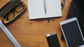 Tabell för kontorsskrivbord med exponeringsglas, bärbara datorn, telefonen, minnestavlan, anteckningsboken och linjalen royaltyfri foto