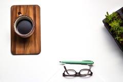 Tabell för kontorsskrivbord med tillförselgarnering och kaffekoppen överkant Arkivbild