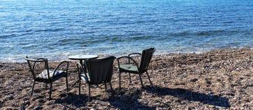Tabell för tre personer på en strand royaltyfria foton