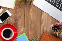 Tabell för kontorsskrivbord med datoren, tillförsel, kaffekoppen och blomman Royaltyfria Bilder