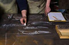 Tabell i en smedja Planera design av kniven Hantverkaren står nära tabellen och teckningen Royaltyfri Fotografi