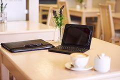 Tabell i ett kafé med en elektroniskt minnestavla och kaffe arkivbilder