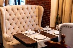 Tabell i ett kafé som tjänar som i ett kafé, en beige soffa för tappning, trätabell royaltyfri fotografi