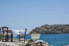 Tabell med bordduken och två stolar nära det blåa vattnet Royaltyfri Fotografi
