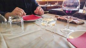 Tabell med den vita skateryuen i restaurang blåa dof-exponeringsglas blir grund wine Royaltyfria Foton
