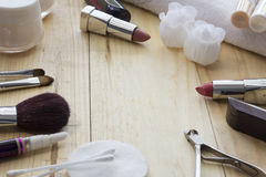Tabell med makeup, borstar, läppstift och kräm arkivbilder