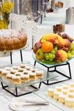 Tabell med olik kakor och frukt Arkivfoto