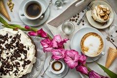 Tabell med påfyllningar av kaffe, kakor, muffin, efterrätter, frukter, blommor och giffel Forntida skedar och ett magasin, fotografering för bildbyråer