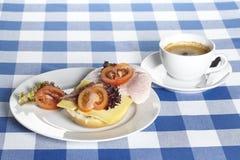Tabell med skinka- och ostrullar och en kopp kaffe Arkivfoto