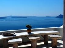 Tabell med stolar i Fira Grekland som förbiser havet Royaltyfri Foto