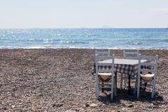 Tabell med stolar på stranden Krog i Grekland, Santorini Arkivfoto