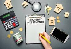 Tabell med trähus, räknemaskin, mynt, förstoringsglas med ordegenskapsinvesteringarna Tilldragning av investering i ditt arkivfoto