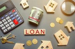 Tabell med trähus, räknemaskin, mynt, förstoringsglas med ordlånet på träkvarter Köpa ett skuldsatt hem kreditering royaltyfri bild