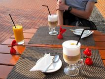 Tabell med två exponeringsglas av cappuccino, orange fruktsaft, tre godisar i rött omslag Royaltyfri Bild