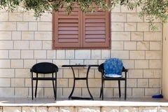 Tabell med två stolar framme av hus Arkivbild