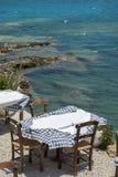 Tabell och tre stolar av den gataGrekland restaurangen på Kreta i den soliga dagen Arkivbilder