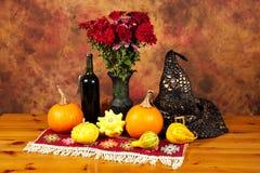 Tabell som dekoreras med den röda filten, höstblommor, flaskan av vin, häxahatten, pumpor och squashar Royaltyfri Bild