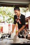 Tabella asiatica della regolazione della cameriera di bar in ristorante Fotografia Stock