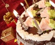Tabella celebratoria (torta e candele di compleanno, contenitori di regalo) su colore rosso Fotografie Stock Libere da Diritti