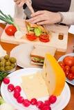 Tabella con alimento e la donna che dividono in due panino Fotografie Stock