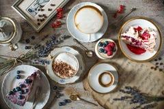 Tabella con i carichi di caffè, dei dolci, dei bigné, dei biscotti, dei cakepops, dei dessert, dei frutti, dei fiori e dei croiss fotografia stock