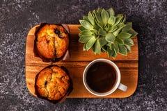Tabella con i muffin, il fiore ed il caffè Fotografie Stock Libere da Diritti