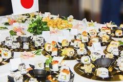 Tabella con i pasti, le carte e la bandiera giapponesi di cucina Immagini Stock