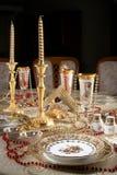 Tabella con i piatti dell'oro Fotografia Stock
