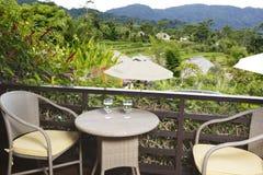 Tabella con i vetri sui terrazzi di trascuratezza e sulle montagne di un riso del balcone aperto Fotografia Stock