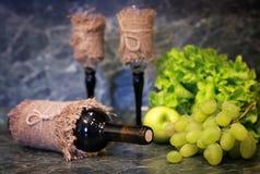 Tabella con l'uva della bottiglia di vino Fotografie Stock