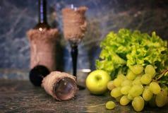 Tabella con l'uva della bottiglia di vino Fotografia Stock