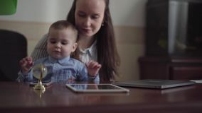 Tabella con la compressa, il telefono cellulare ed il computer portatile La giovane madre con il piccolo neonato si siede sulla t video d archivio