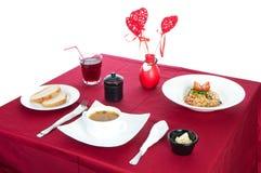 Tabella con la tavola servita con la prima colazione e la bevanda, rosso della tovaglia, coltelleria Chiuda su, dell'interno fotografia stock libera da diritti