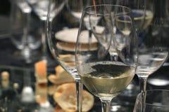 Tabella con molti vetri di vino bianco Fotografia Stock