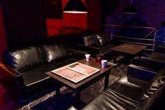 Tabella con tavola reale e tè nel caffè con illuminazione scura per lo svago con una progettazione moderna Immagine Stock